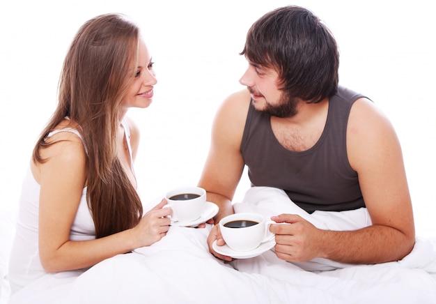 ベッドでコーヒーを飲む若いカップル