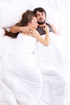 若いカップルがベッドで眠る