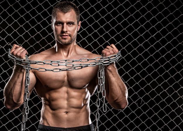 フェンスに鎖を持つ男