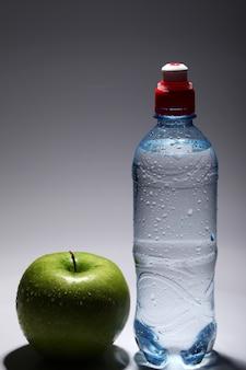 Бутылка свежей холодной воды и зеленого яблока