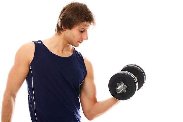 Молодой спортивный человек со спортивной одеждой держит гантели