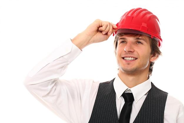 産業用ヘルメットを持つ若い労働者の男のポートレート
