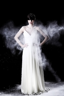 Красивая женщина в белом платье и летающей пыли