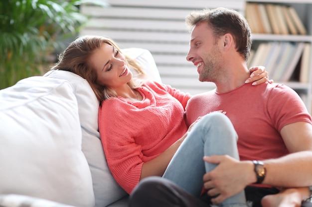 ソファで一緒に時間を楽しんでいる素敵なカップル
