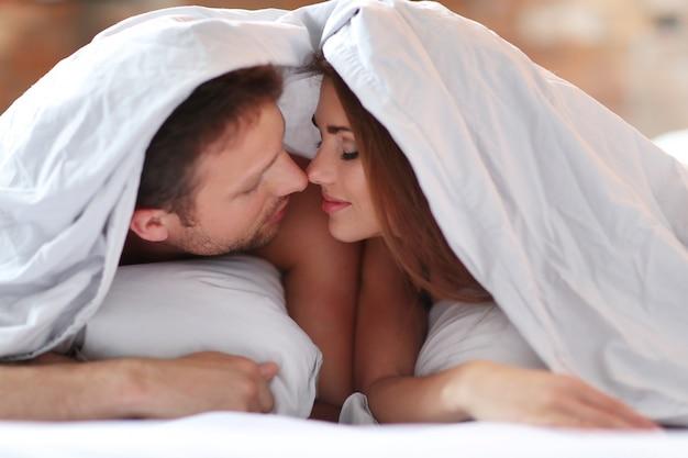カバーの下のベッドでの素敵なカップル。