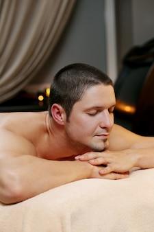 Красивый мужчина расслабляющий в спа