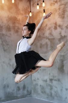 Молодая балерина прыгает в воздухе