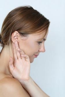 耳に手を持つ美しい女性