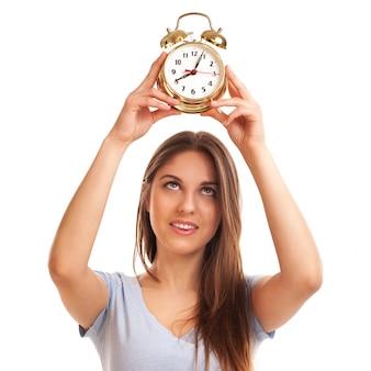 目覚まし時計を持つ若い白人女性