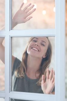 Красивая молодая женщина позирует за окном