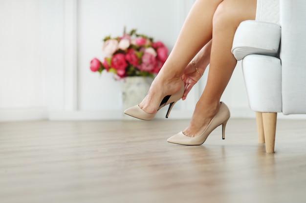 Женщина сидит на кресле и носит бежевые каблуки