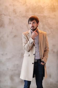 ベージュのコートを着ているハンサムな男