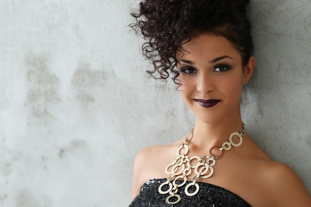 Прекрасная молодая женщина с черными вьющимися волосами и черным блестящим платьем