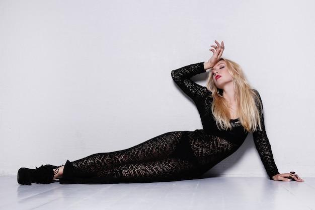 Красивая женщина позирует в черном сетчатом платье