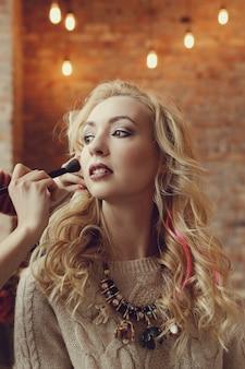 美しい金髪の女性とメイクアップアーティスト