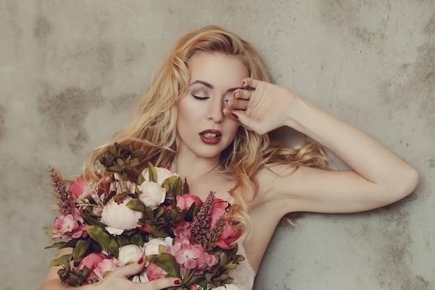 バラの花束を保持している豪華な女性