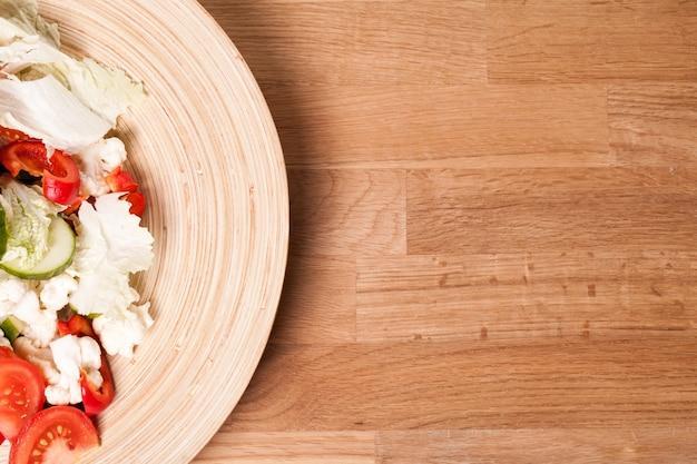 Деревянная тарелка с овощным салатом