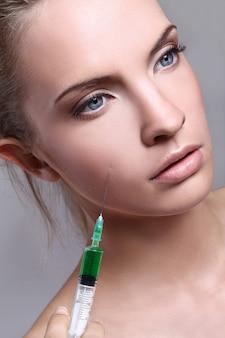 Молодая женщина, впрыскивая для косметических процедур