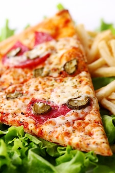 フライドポテトと新鮮なピザのクローズアップ表示