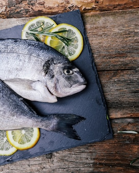 素朴なボード上のレモンと新鮮な魚
