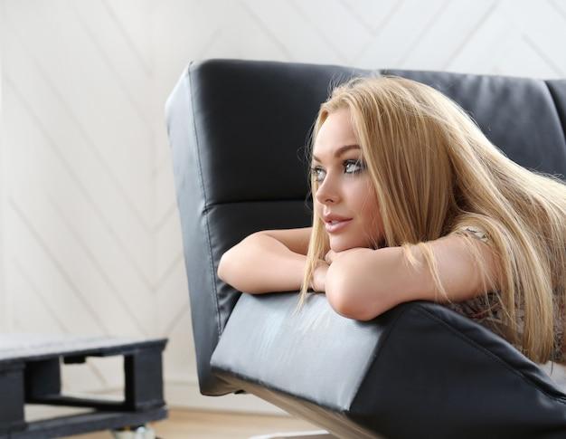 ソファーで横になっている美しい金髪の女性の肖像画