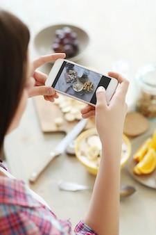 彼女の健康的な朝食の写真を撮る女性