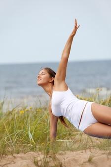 Женщина делает йогу на пляже