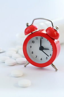 Ретро будильник и белые таблетки крупным планом. здравоохранение