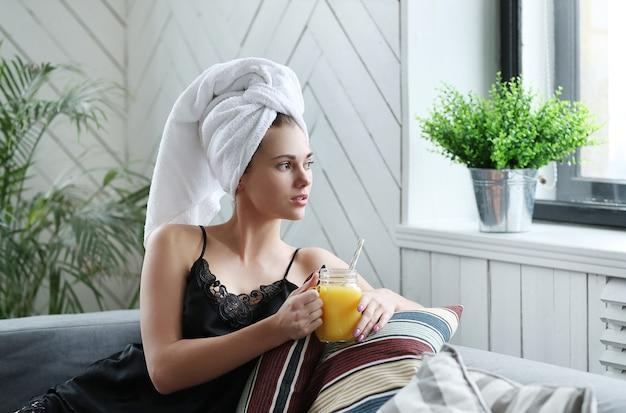 彼女の頭とオレンジジュースにタオルを持つ若い女性