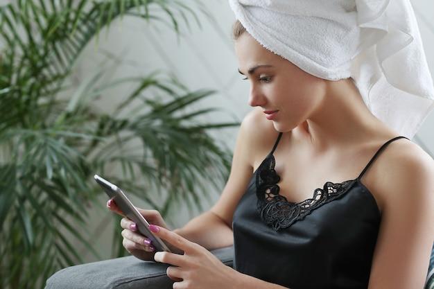 デジタルタブレットを使用して、彼女の頭にタオルを持つ若い女性