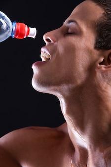 冷たい水のボトルを持つ若い男