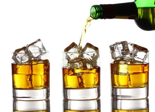 グラスにウイスキーを注ぐ