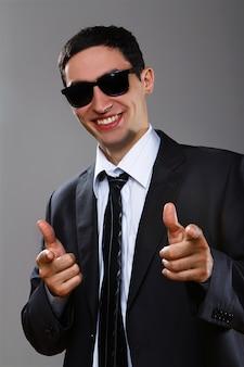 あなたを指しているサングラスで幸せなビジネスマン