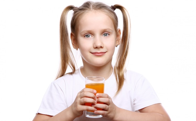 新鮮なオレンジジュースのガラスを保持しているかわいい女の子