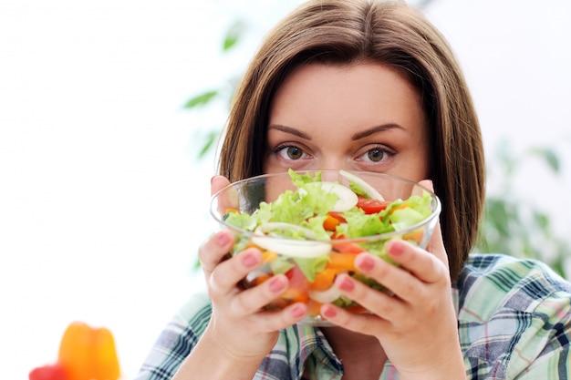 Счастливая женщина с миской свежего салата
