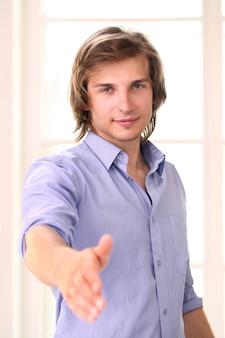 Красивый мужчина предлагает пожать ему руку