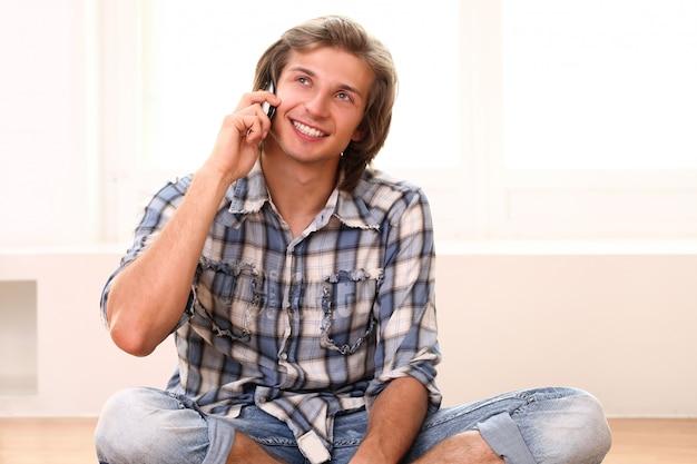 床に座って電話で話している男性