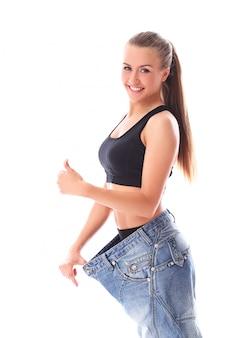 減量後の古いジーンズを着ている女性
