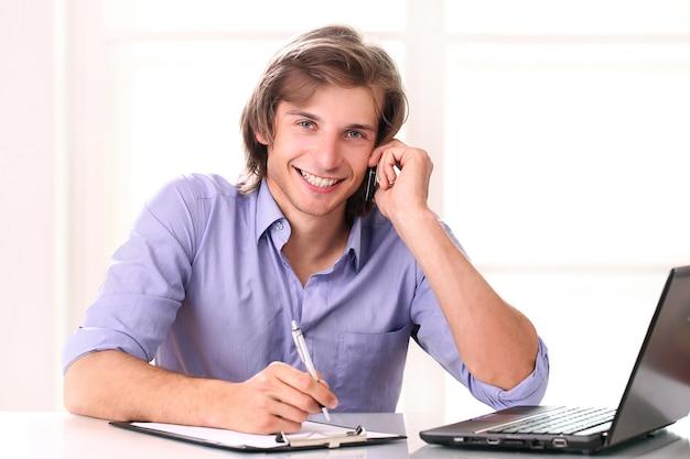 Красивый мужчина звонит по мобильному телефону