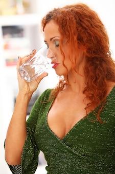Рыжая женщина пьет воду