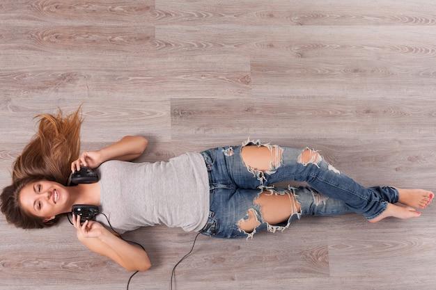 床に横たわってヘッドフォンで美しい女性