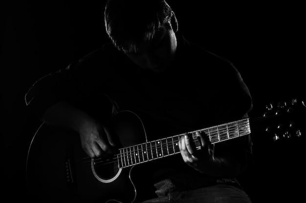 暗闇の中でギターを持つ男