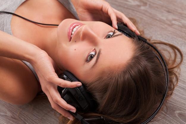 Женщина лежит на полу с наушниками