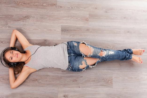 ヘッドフォンで床に横たわっている女性