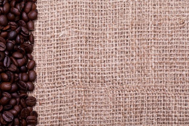 Кофе в зернах над тканевым мешком