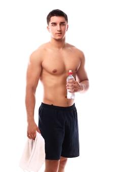 タオルと水のボトルを持つ筋肉男