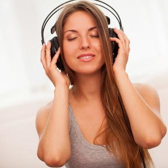 美しい女性は、ヘッドフォンで音楽を楽しむ