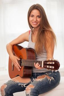 ギターを弾く若い美しい女性
