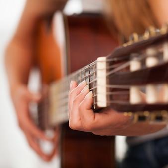 Макрофотография изображение гитары в руках женщины