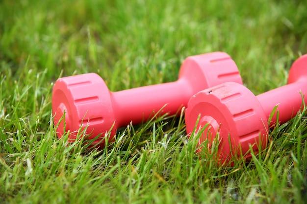 草の上のピンクの女性のダンベル